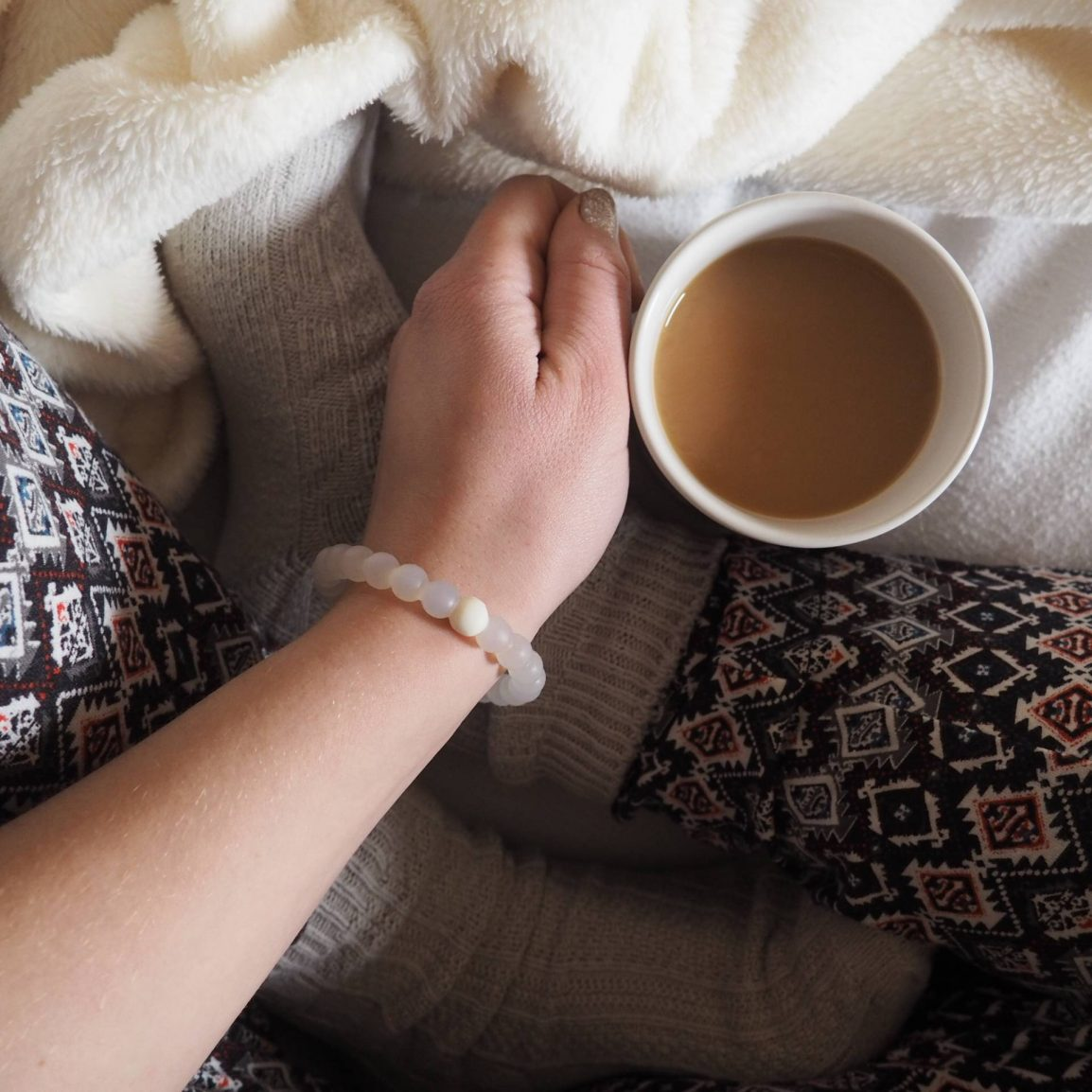 Girl sitting with a cup of tea with legs crossed and a blanket