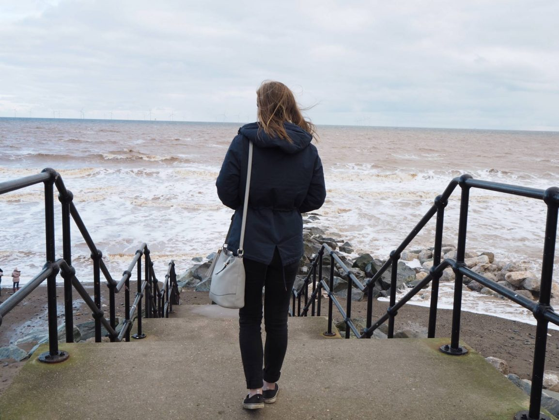 girl walking onto the beach from Withernsea Pier