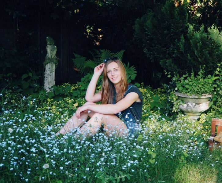 girl sitting in rural garden surrounded by blue flowers