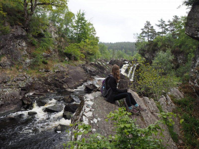 Girl enjoying walking trails around Rogie Falls in Scotland